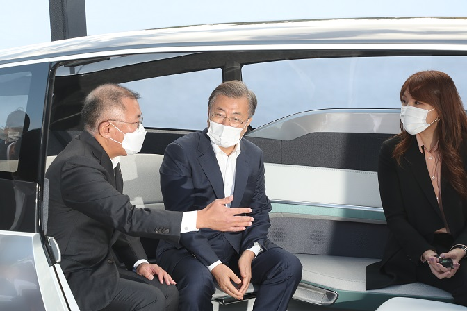 Hyundai Group Chairman Chung Euisun (L) shares his company's next-generation car vision with South Korean President Moon Jae-in (C) aboard a self-driving concept car at Hyundai's factory in Ulsan, 414 kilometers southeast of Seoul, on Oct. 30, 2020. (Yonhap)