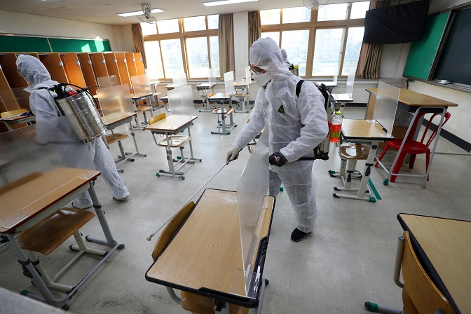 Health workers disinfect a school in the southeastern city of Daegu on Nov. 26, 2020, amid a resurgence of the coronavirus ahead of the national college entrance exam slated for Dec. 3. (Yonhap)