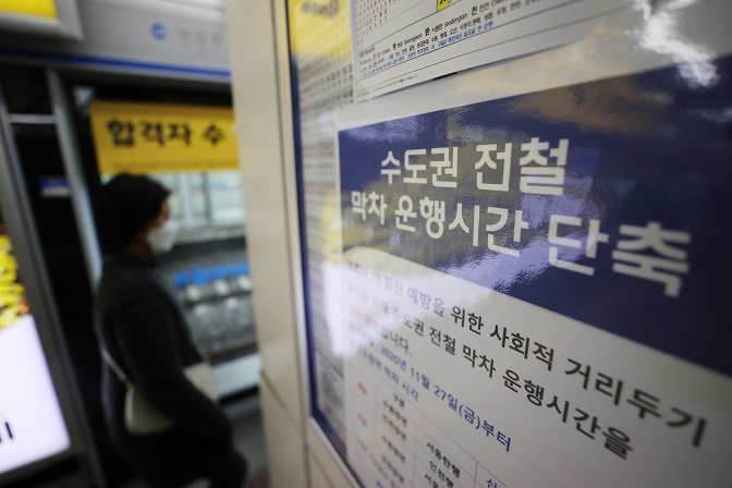 This photo, taken Nov. 27, 2020, shows a notice at Seoul's Sindorim Station announcing reduced subway services due to COVID-19. (Yonhap)