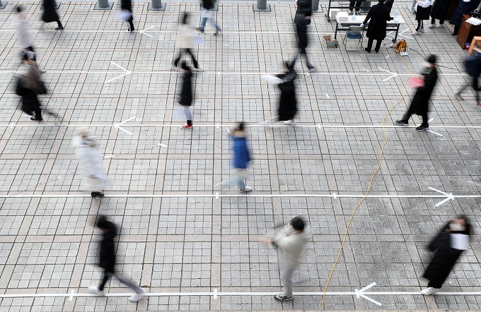 Students keep a distance from one another while waiting in line to receive their test identification slips in the schoolyard at a high school in Daejeon, 164 kilometers south of Seoul, on Dec. 2, 2020, one day ahead of the country's nationwide college entrance test amid the coronavirus pandemic. (Yonhap)