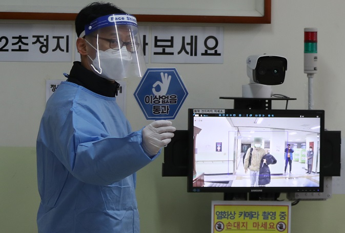 A teacher in quarantine gear checks students' temperatures at a high school in Masan, South Gyeongsang Province, on Dec. 3, 2020, before the nationwide college entrance exam begins. (Yonhap)
