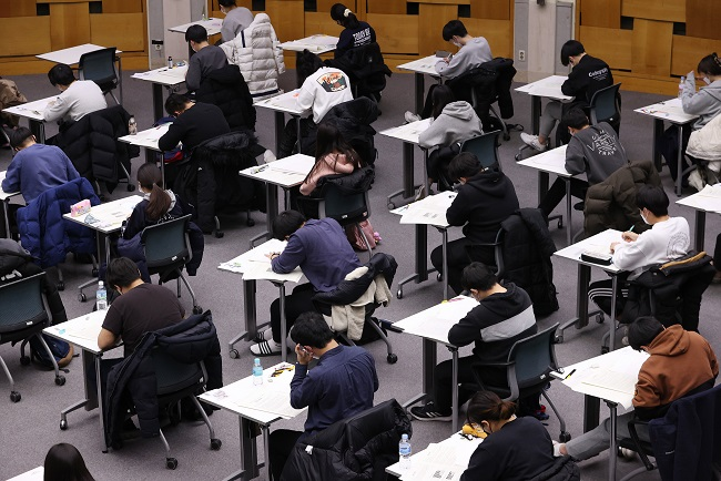 Applicants take an essay test at Konkuk University in Seoul on Dec. 5, 2020, in a follow-up college entrance exam after the state-administrated College Scholastic Ability Test on Dec. 3. They sit apart as a precaution against the coronavirus. (Yonhap)