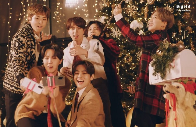 """This photo, provided by Big Hit Entertainment, shows BTS singing in the music video for the holiday remix version of its hit song """"Dynamite."""""""