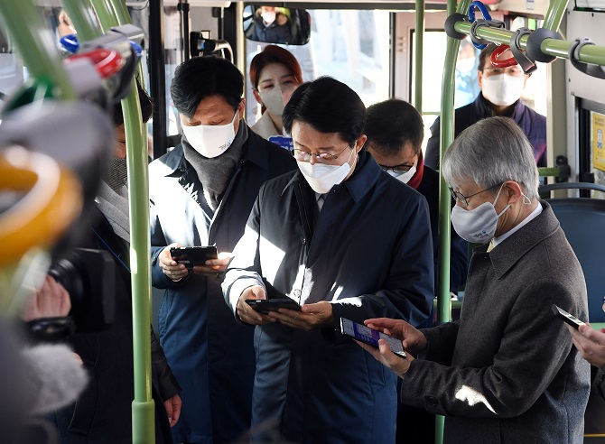 ICT Minister Choi Ki-young (R) and two ruling party lawmakers access free Wi-Fi services on a bus in Seoul on Dec. 14, 2020, as South Korea has established the network on all city buses in operation in the country. (Yonhap)