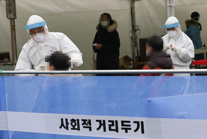 Medical workers collect specimens from people for COVID-19 tests at a temporary screening facility in front of Seoul Station on Dec. 18, 2020. (Yonhap)