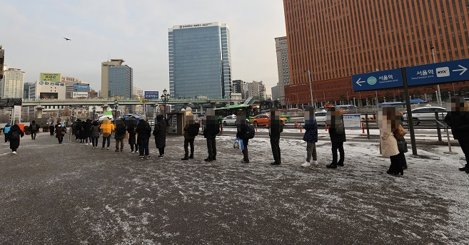 People stand in line for COVID-19 testing at a temporary screening station in front of Seoul Station on Dec. 18, 2020. (Yonhap)