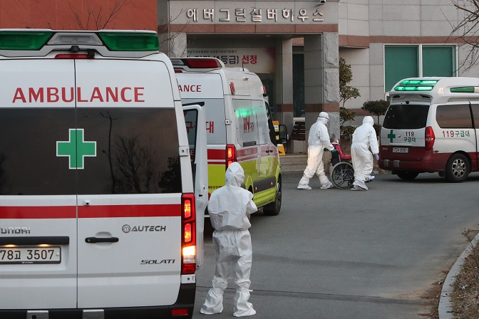 A COVID-19 patient is loaded into an ambulance at a nursing home in the southwestern city of Gwangju on Dec. 22, 2020, to be transported to a nearby hospital. Twelve residents and four workers have been diagnosed with the new coronavirus at the facility. (Yonhap)