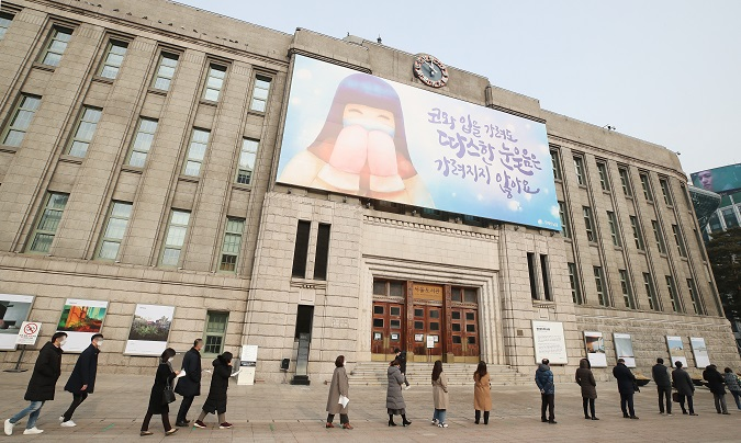 People line up to receive coronavirus tests at a makeshift clinic in Seoul on Dec. 23, 2020. South Korea's daily new coronavirus cases rose to above 1,000 for the first time in three days the same day. (Yonhap)
