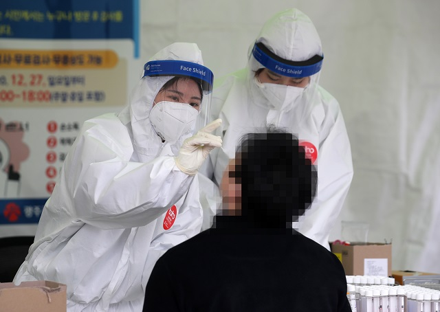 Medical workers collect a specimen from a man for a coronavirus test at a virus treatment center in Gwangju, 330 kilometers southwest of Seoul, on Dec. 29, 2020. (Yonhap)