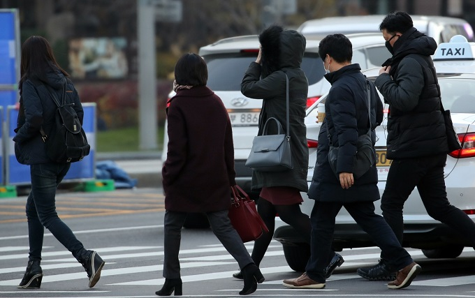 Citizens in thick winter jackets walk near Gwanghwamun Square in downtown Seoul on Nov. 30, 2018. (Yonhap)
