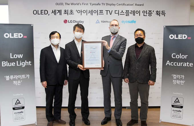 This photo provided by LG Display Co. on Jan. 5, 2020, shows officials from LG Display and TUV Rheinland posing for a photo in Seoul after the company's OLED panel won Eyesafe certification.
