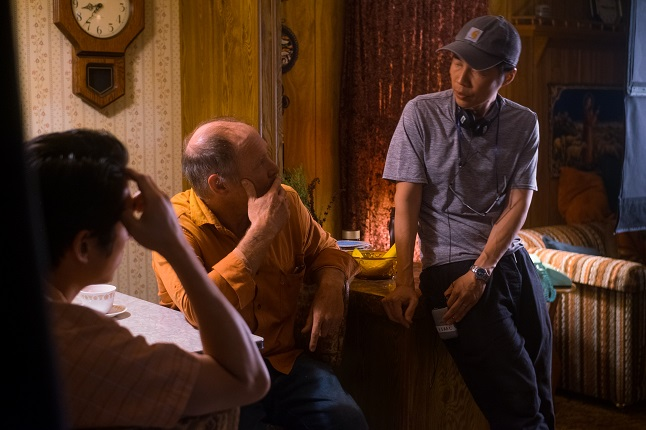 """In this photo taken by Melissa Lukenbaugh and provided by A24, director Lee Isaac Chung (R) of """"Minari"""" talks with actors Will Patton (C) and Steven Yeun (L)."""