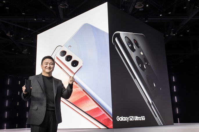 This photo provided by Samsung Electronics Co. on Jan. 15, 2021, shows Roh Tae-moon, who heads Samsung's mobile business, holding the Galaxy S21 smartphone at the Galaxy Unpacked 2021 event.