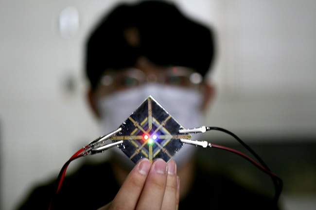 This photo provided by Samsung Display Co. on Jan. 26, 2021, shows a researcher from the company testing OLED organic material.