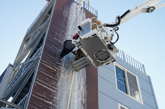 This photo provided by Sejong Fire Department shows its rescuers removing large icicles on a building.