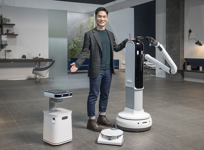 This photo provided by Samsung Electronics Co. on Jan. 11, 2021, shows Sebastian Seung, head of Samsung Research, introducing Samsung Bot Handy (R), JetBot 90 AI+ vacuum cleaner (C) and Samsung Bot Care at the company's online press event for the all-digital Consumer Electronics Show 2021.