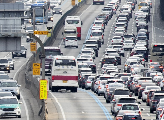 In this file photo, a long queue of vehicles moves at a snail's pace on both sides of the Gyeongbu Expressway on Jan. 26, 2020, as many hit the road to celebrate the Lunar New Year holiday. (Yonhap)