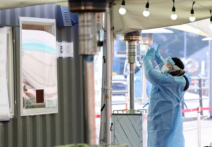 A medical worker warms herself under a gas heater at a makeshift clinic for coronavirus tests in front of Seoul Station on Jan. 1, 2021, amid a cold snap hitting the country. (Yonhap)