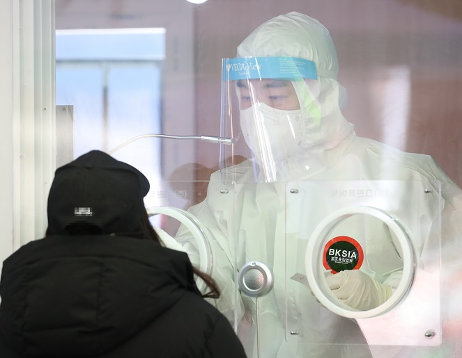 A medical worker collects a specimen from a woman at a temporary COVID-19 screening station in front of Seoul Station on Jan. 3, 2021. (Yonhap)