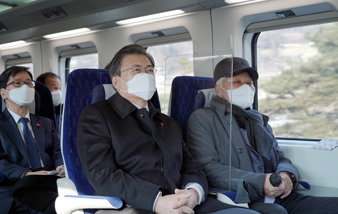 President Moon Jae-in (L, front) takes a trial ride in the KTX-Eum environment-friendly high-speed train on Jan. 4, 2021. (Yonhap)