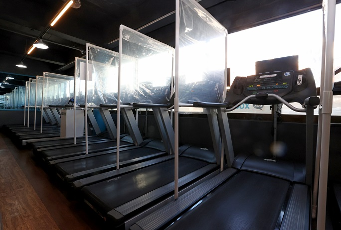 Partitions are set up between treadmills in a gym in western Seoul on Jan. 7, 2021, as part of antivirus efforts. (Yonhap)