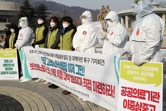 Members of the Korean Health and Medical Workers' Union hold a news conference in front of Cheong Wa Dae in Seoul on Jan. 12, 2021, to call on the government to increase compensation for medical workers at COVID-19-fighting public hospitals. (Yonhap)