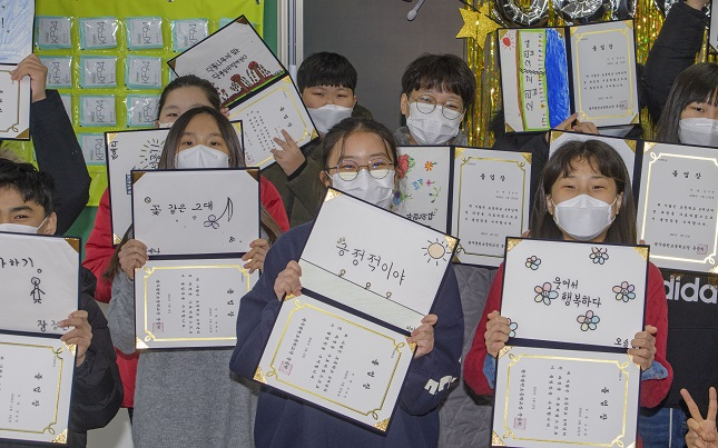 Students pose for a photo during a graduation ceremony at Gwangcheon Elementary School in Gwangju on Jan. 12, 2021. (Yonhap)