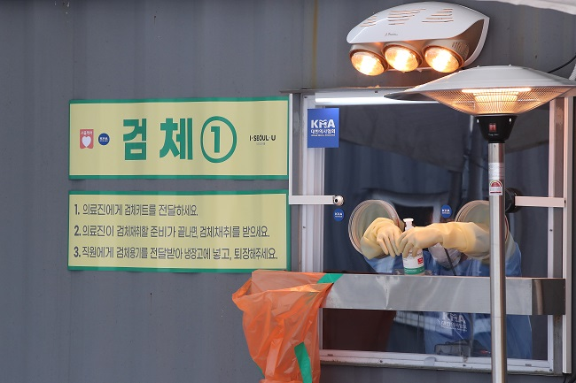 Medical officials prepare to carry out COVID-19 tests at a makeshift clinic in Seoul on Jan. 14, 2021. (Yonhap)