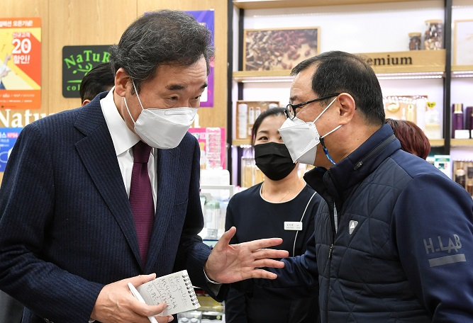 This photo provided by the National Assembly press corps shows Democratic Party Chairman Rep. Lee Nak-yon talking to a business owner in Seoul on Jan. 14, 2021, while inspecting business establishments hit by the new coronavirus pandemic.