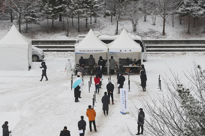 People wait in line to receive virus tests at a makeshift COVID-19 testing facility in Uijeongbu, north of Seoul, on Jan. 18, 2021. (Yonhap)