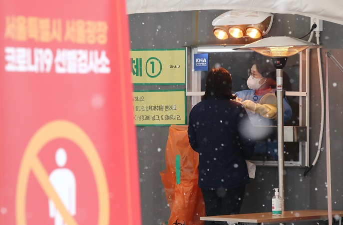 A health worker collects a sample from a citizen at a makeshift COVID-19 testing facility amid snowfall in Seoul on Jan. 18, 2021. (Yonhap)