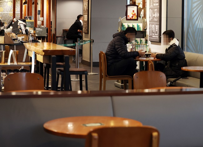Customers are seated inside a cafe in central Seoul on Jan. 18, 2021, after the government eased COVID-19 restrictions to allow coffee shops to offer dine-in services. (Yonhap)