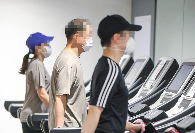 People walk on treadmills at a gym in Seoul on Jan. 18, 2021, as health authorities eased restrictions on cafes, gyms and other indoor facilities the same day amid signs of a letup in new coronavirus cases. (Yonhap)