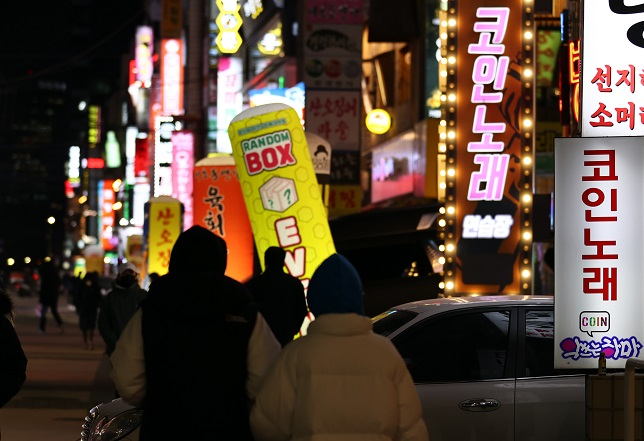Signs for coin-operated karaoke rooms are illuminated in Seoul on Jan. 18, 2021, as health authorities eased restrictions on cafes, gyms and other indoor facilities the same day amid signs of a letup in new coronavirus cases. (Yonhap)