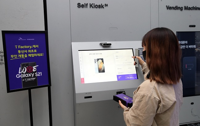 This file photo, taken Jan. 22, 2021, shows a customer at SK Telecom Co.'s store in western Seoul receiving Samsung Electronics Co.'s Galaxy S21 smartphone from a digital kiosk. (Yonhap)