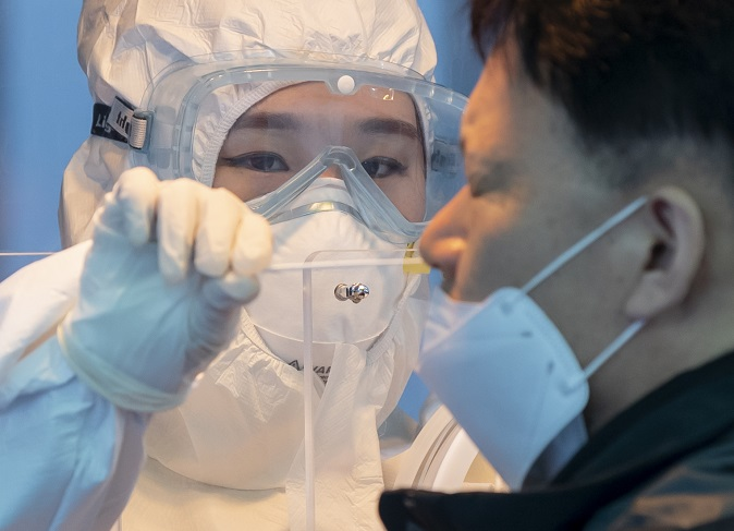 A health worker clad in a protective suit collects a sample from a citizen at a makeshift virus testing clinic in Seoul on Jan. 22, 2021. (Yonhap)