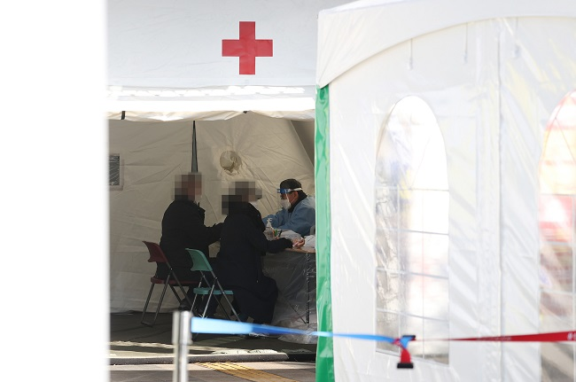 Visitors receive a coronavirus test at a temporary screening center set up at a health community center in the central Seoul ward of Yongsan on Jan. 24, 2021. (Yonhap)