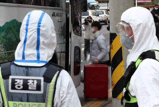 Virus patients tied to a religious educational facility in the central city of Daejeon, 164 kilometers south of Seoul, get on a bus on Jan. 25, 2021, to move to a treatment center, with police officers standing nearby. (Yonhap)