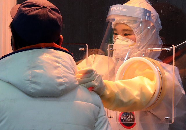 A medical worker collects a sample from a visitor at a COVID-19 screening station in Seoul on Jan. 26, 2021. (Yonhap)