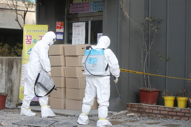 Health workers conduct disinfection work around a religious educational facility in Gwangju, about 330 kilometers south of Seoul, on Jan. 27, 2021. (Yonhap)