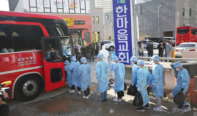 People who tested positive for the new coronavirus from a religious educational facility in Gwangju, about 330 kilometers south of Seoul, get on a bus headed to a treatment center on Jan. 27, 2021. (Yonhap)