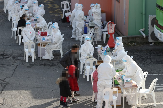 A citizen and his children wait for their turn to get virus tests in Gwangju, 329 kilometers south of Seoul, on Jan. 28, 2021. (Yonhap)