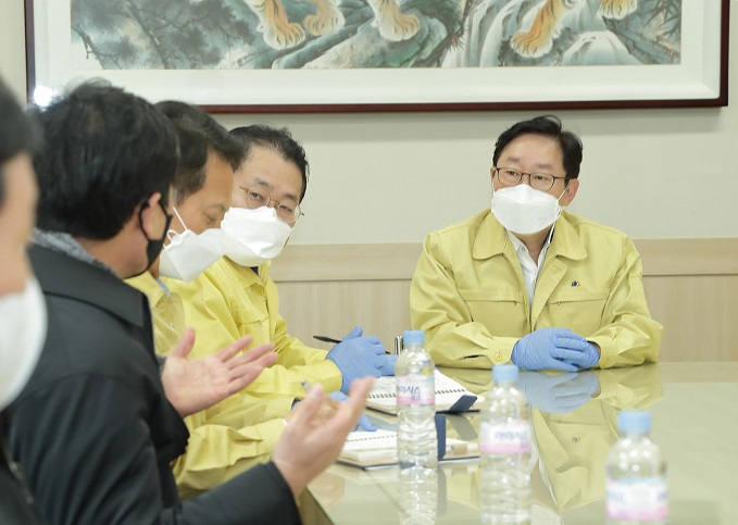 Justice Minister Park Beom-kye (R) listens to a business executive during his visit to an industrial complex, northeast of Seoul, on Feb. 19, 2021, where massive coronavirus infections of foreign workers were reported, in this photo provided by his office.