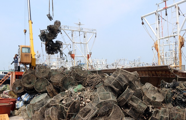 Work to move discarded fishing gear onto a pier is under way in the western port city of Boryeong on July 2, 2020. The waste was retrieved by local fishermen from under seas off the port in a campaign to clean the seas. (Yonhap)