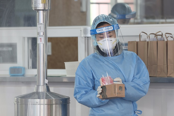 A medical worker holds COVID-19 test kits at a makeshift clinic in Seoul on Feb. 22, 2021. (Yonhap)