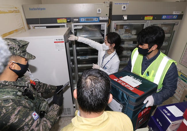 An official gives a box containing AstraZeneca's vaccine to a medical worker under the escort of the military and police after arriving at a public health center on the country's southern Jeju Island on Feb. 25, 2021, one day ahead of the start of COVID-19 vaccinations. (Yonhap)