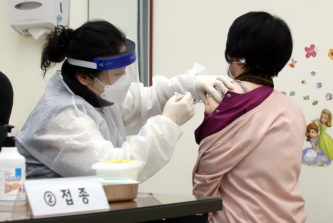 A citizen (R) receives a shot of AstraZeneca's COVID-19 vaccine at a public health center in Incheon, 50 km west of Seoul, on Feb. 26, 2021, when the country kicked off its nationwide vaccinations at 9 a.m. More than 5,000 medical workers and patients aged under 65 at long-term care facilities were the vaccine's first recipients. (Yonhap)