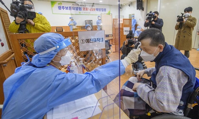 A patient (R) of a convalescent hospital in Gwangju, southwestern South Korea, undergoes a fever check before getting a COVID-19 vaccine shot on Feb. 26, 2021, in this joint press corps photo. (Yonhap)