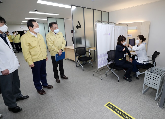 Chung Mi-kyeong (2nd from R), a sanitation worker of the National Medical Center, receives a Pfizer vaccine at the hospital in central Seoul on Feb. 27, 2021, while Prime Minister Chung Sye-kyun (2nd from L) looks on. She became the first South Korean to get the Pfizer product. (Yonhap)