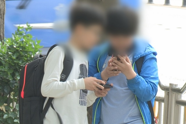 This captured image from Yonhap News TV shows children looking at their smartphones on a street.